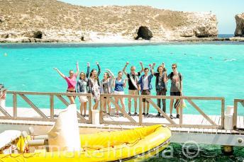 A tanulók egy csoportja integet a hajó mellett a Kék-Lagúnában, Cominón