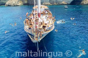 Angolul tanuló diákok agy máltai hajókiránduláson éppen a tengerbe ugranak