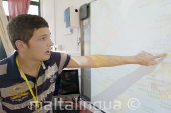 Tanuló egy térképre mutat az osztályteremben