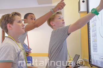 Egy tanár segít 2 diákot az interaktív fehér táblánál