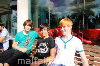 3 diák egy padon ül a diákszálló előtt