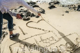 Egy diák a homokba rajzolja: Én 'szív' Maltalingua