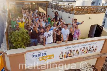 Angolul tanuló diákok integetnek a tetőteraszról