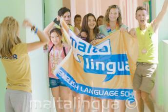 A tanulók egy csoportja zászlót lobogtat a nyári nyelvi táborunkban