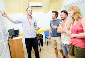 A tanár az interaktív fehértáblát használva magyaráz