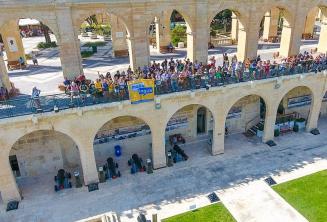 Maltalingua tanulók integetnek a Felső Barrakka-kertben, Vallettában