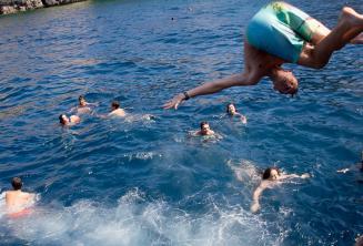 Egy tinédzser tanuló szaltózik a tengerbe