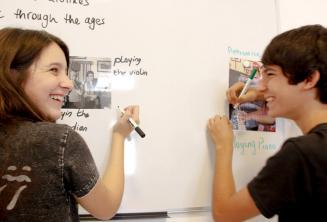 Két diák közösen old meg egy feladatot a táblánál
