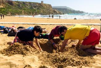 A csoportvezető a gyerekekkel gödröt ás a strandon