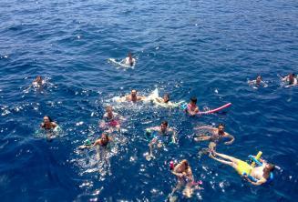 Az angolul tanuló diákok egy nagy csoportja együtt úszik