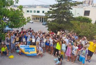 A junior tanulók egy nagy csoportja integet a nyári iskola előtt