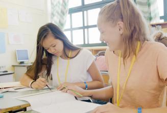 2 lányok közösen dolgozik egy angol nyelvi feladaton azt osztályteremben